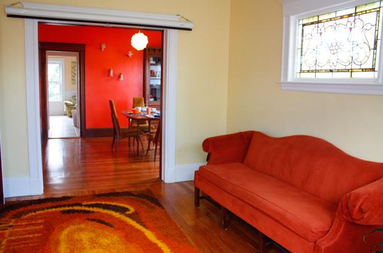 Met de oranje bank en het gekleurde vloerkleed is gekozen voor een wat ...